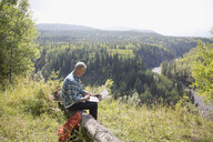Mature man hiking resting using laptop on log at sunny remote rural hilltop - HEROF13537