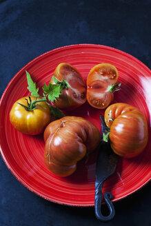 Chocolate Stripes Tomaten, Tomaten (Solanum lycopersicum), amerikanische Tomaten, Fleisch-Tomaten,braun-rot, grün, gestreift,  dunkler Untergrund, Messer, roter Teller - CSF29239