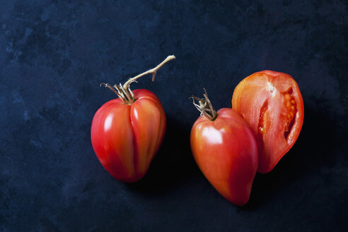 Whole and sliced Oxheart tomatoes on dark ground - CSF29278