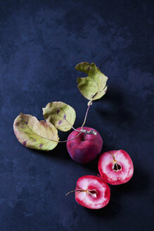 Sliced and whole red-fleshed apples on dark ground - CSF29290