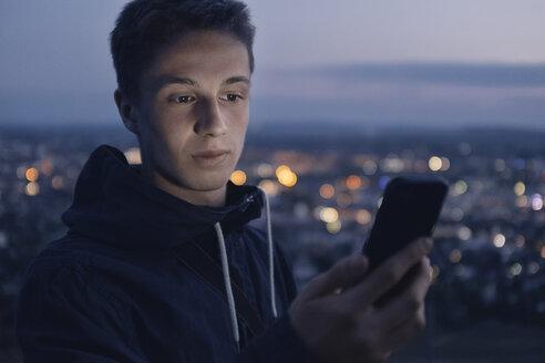 junger Man mit Smartphone bei Dämmerung mit den Lichtern einer Stadt im Hintergrund, Wartberg, Deutschland, Baden-Würtemberg, Heilbronn - GCF00239