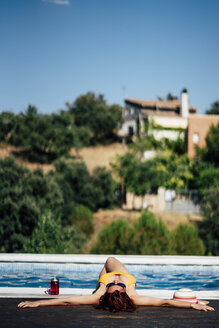 Pretty woman in a swimsuit next to the edge of the pool. Spain. - OCMF00246