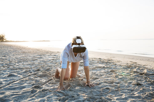 pretty blonde woman using virtual 3D glasses on a beach in Thailand, in the morning light - HMEF00185