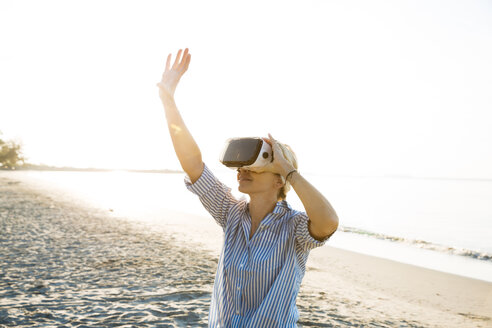 pretty blonde woman using virtual 3D glasses on a beach in Thailand, in the morning light - HMEF00188
