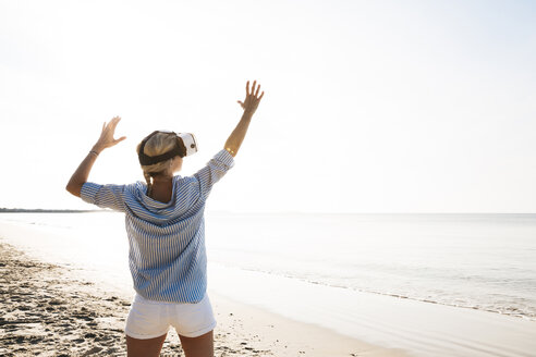 pretty blonde woman using virtual 3D glasses on a beach in Thailand, in the morning light - HMEF00197