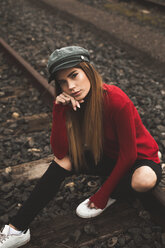 Portrait of young woman wearing red pullover sitting on rail - ACPF00401
