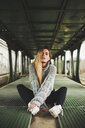 Portrait of young woman sitting in an abandoned train car - ACPF00404