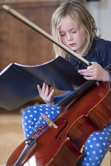 Portrait of blond girl with cello and bow looking at musical notes - HAMF00561