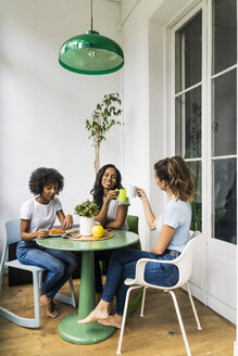 Three happy women sitting at table at home drinking coffee together - GIOF05626