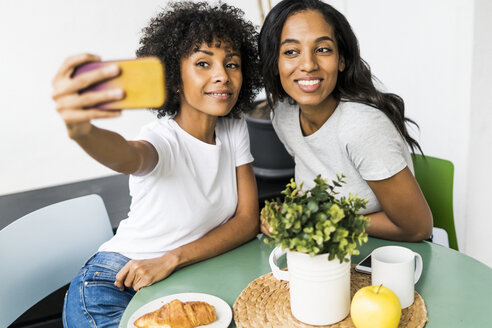 Two happy girlfriends sitting at table taking a selfie - GIOF05629