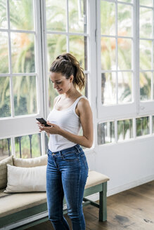 Smiling woman checking cell phone at the window at home - GIOF05638