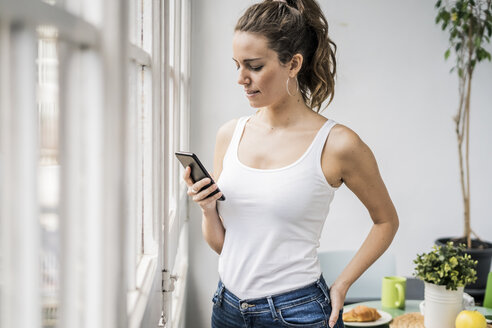 Woman checking cell phone at the window at home - GIOF05641