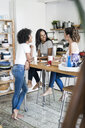 Three happy women socializing at kitchen table at home - GIOF05644