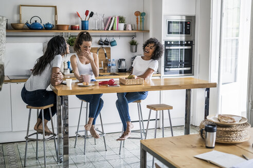 Three happy women sitting at kitchen table at home socializing - GIOF05647