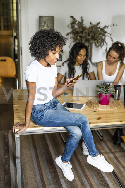 Woman with cell phone sitting on table with friends in background - GIOF05659