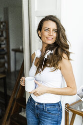 Smiling woman with cup of coffee and headphones at home - GIOF05665