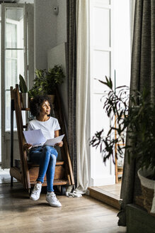 Woman sitting on steps at home with document - GIOF05668