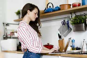 Woman using laptop in kitchen at home - GIOF05677