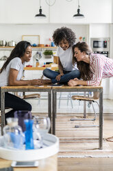 Three smiling women looking at tablet on table at home - GIOF05686