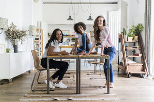 Portrait of three happy women at table at home - GIOF05692