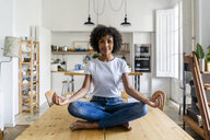 Portrait of smiling woman in yoga pose on table at home - GIOF05698