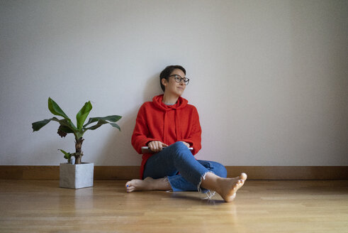 Young woman sitting on floor, daydreaming - MOEF01969