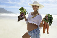 Portrait of smiling pregnant woman on the beach holding carrots and beetroot - ECPF00305