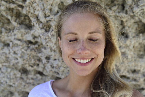 Portrait of smiling blond woman with closed eyes in front of rocky background - ECPF00311