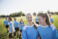 Smiling middle school girl soccer players laughing on sunny field - HEROF13556