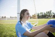 Smiling middle school girl soccer player holding soccer ball at goal net post - HEROF13565