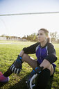 Serious middle school girl soccer goalie listening to music with headphones and mp3 player on sunny field - HEROF13568