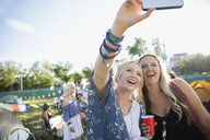 Smiling young women taking selfie at summer music festival campsite - HEROF13577
