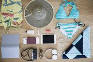 Still life bikini and vacation items on hardwood floor - HEROF13610
