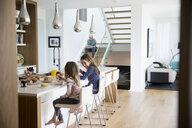 Sisters eating breakfast at kitchen island - HEROF13613
