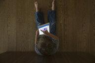 View from above boy drawing on digital tablet on hardwood floor - HEROF13619