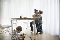 Son kissing mother working at laptop in dining room - HEROF13622