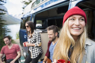 Smiling woman with friends outside camper van at lakeside - HEROF13637