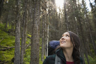 Smiling woman hiking with backpack in woods looking up at trees - HEROF13643