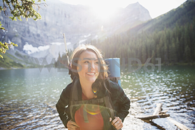 Smiling woman hiking with backpack at sunny remote lakeside - HEROF13646