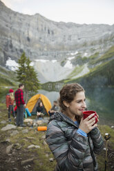 Smiling woman drinking coffee looking away at remote mountain lakeside campsite - HEROF13649