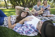 Smiling couple laying in grass in summer park - HEROF13670