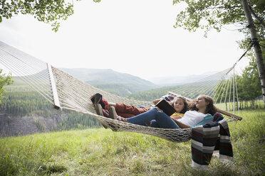 Sisters laying in rural hammock reading book - HEROF13679