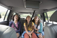 Sisters watching movie laughing in back seat of SUV - HEROF13682