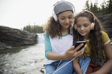 Sisters listening to music with headphones and mp3 player at waterfall - HEROF13685