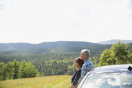 Serene affectionate couple leaning on car looking at sunny rural view - HEROF13688