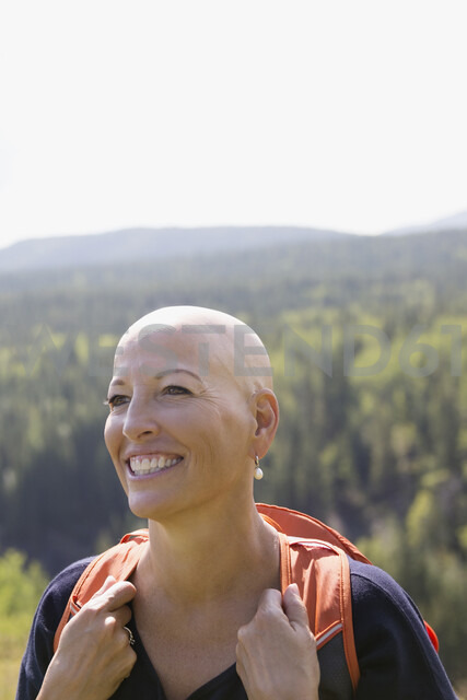Smiling female cancer survivor with shaved head hiking with backpack in sunny woods - HEROF13691 - Hero Images/Westend61
