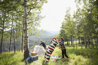 Senior couple preparing campsite in sunny rural field - HEROF13694