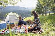 Senior couple enjoying picnic on blanket at campsite - HEROF13697