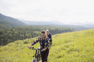 Senior couple walking mountain bikes in sunny remote rural field - HEROF13703