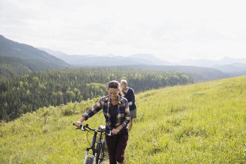 Senior couple walking mountain bikes in sunny remote rural field - HEROF13703